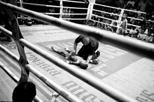 A boy  has lost the boxing match and is lying unconscious on the ground. © Sandra Hoyn