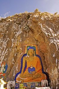 This rock carving of the Medecine Buddha is near Nyethang, Tibet. It's about 40 feet high and is surrounded by white prayer scarves left by pilgrims. Photographed on 30 June 2005. © Forest McMullin