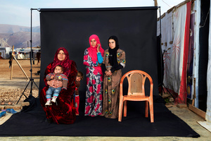 Portrait of a Syrian refugee family in a camp in Bekaa Valley, Lebanon, on 15 December 2015. The empty chair in the photograph represents a family member who has either died in the war or whose whereabouts are unknown.