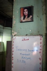 The portrait of Ankita hangs in one of the community offices used by The Humsafar Trust. Ankita was a guru who died of an infection 15 days after being castrated in a hospital.  Below on the white board is a reminder about a two day training session for the hijras.  © Alison McCauley