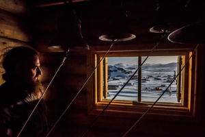 A priest looks on in the Bell room, after a vigil at the Russian Orthodox Church of the Holy Trinity; Fildes Bay, Antartica, 03 December 2015.
