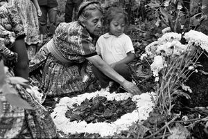 Maria and her grandmother prepare an altar on a recently exhumed grave. The vast majority of the relatives looking for their family members, indeed the vast majority of the victims of the war, are indigenous Mayan. Each day they construct an altar to the dead above the earth they were pulled from. © Victor Blue, 2004