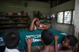 "Keeke, 42, a seller in a local shop in Eita village. Keeke lost her 2-year-old daughter in 2012, the young girls drowned in a high tide while playing alone. ""It's very painful for me and my husband to talk about it. We didn't have seawall near our house, we still don't have it. It's too expensive for us to built it, we simply don't have money""."