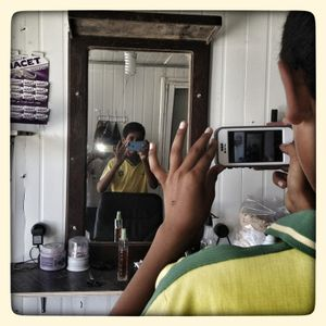 Khaled* takes a photo of Salem* in the barbershop in Za'atari refugee camp.