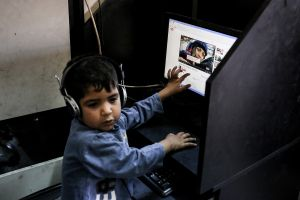 """Cyber cafes have become a popular source of entertainment for Syrian kids. For one Turkish lira, they can use the internet for half an hour. The kids get the money by begging and then spend it playing games, watching music videos, etc. A 3-year old boy came here to watch a TV series named """"Sefkat tepe"""" on Youtube. © Turjoy Chowdhury"""