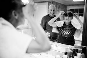 Late one evening, Howie cuts Laurel's hair, knowing that it will start falling out on its own in the coming weeks as a side effect from the chemotherapy. Chappaqua, New York. February 2013 © Nancy Borowick