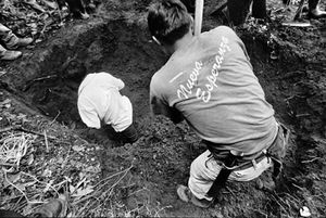 Men from the town of Comalapa dig furiously as they help open a new grave at the ex-military base. The townsfolk value immensely the work of the anthropologists, who also realize the importance of their work to the healing of the communities affected by the violence of the war. © Victor Blue, 2004