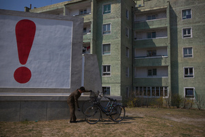 A man checks his bicycle next to a painted exclamation point on a propaganda billboard in Kaesong, North Korea, 24 April 2013.