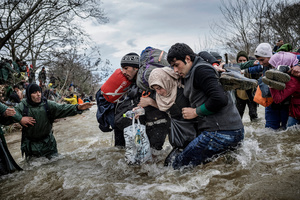 """Migrants cross the river """"Konska"""" on the Macedonia - Greece borders after leaving the Idomeni refugee camp on March 14, 2016."""