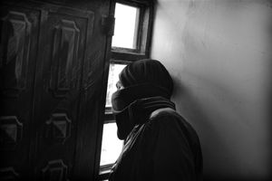 A Palestinian local hides in a local youth centre when live rounds were fired by soldiers, he wears a scarf wrapped round his face to reduce the effects of tear gas. © Will Hilton
