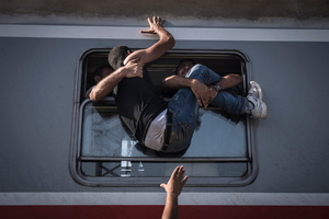 Refugees attempt to board a train headed to Zagreb, Croatia in Tovarnik, Hungary, 18 September 2015.