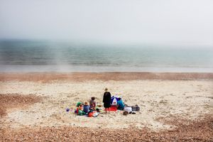 """""""It is mid-afternoon. The weather is sunny. Travelling in the south of England, I am walking on Hayling beach. A sudden fog comes down on the beach changing dramatically its atmosphere. A feeling of strangeness. I take a photograph of this family as I walk past. A few minutes later, the fog disappears, as fast as it came."""""""