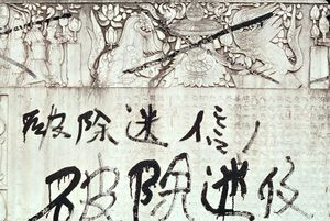 "November 1966. Graffiti written by red guards on a tombstone representing buddhist sculptures. ""Against religious superstitions.""  © Solange Brand"