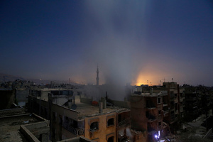 Smoke rises from a building following reported shelling by Syrian government forces in Douma, Syria, 30 October 2015.
