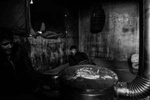 Refugee warms himself by the stove in temporary shelter at the back main train station in Belgrade, Serbia.