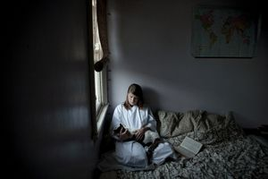 Bedtime bible reading   A priests daughter dressing in her fathers cassock alb. © Liz Hingley