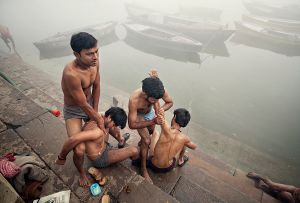 Varanasi, India: Young Brahmans, members of the highest Indian caste, on the shores of the sacred river of Ganges at sunrise massaging each other. Later on they will ritually bathe and clean themselves. © Matjaz Krivic