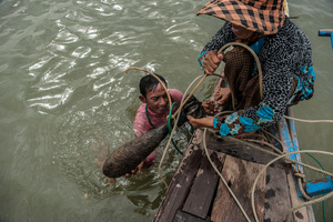 A fisherman and his wife pull out an unexploded mortar round from the river Mekong near Phnom Penh, Cambodia. Fishermen often dive into the rivers using compressed air created by a diesel generator to un-snag their nets when they get caught on the bottom of the river.
