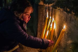 A girl lights candles at the procession of S.Agata in Catania