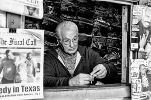 Newsstand vendor rolls a cigarette.