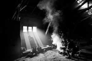 Men gather around a fire at the barracks ,during the meal. Belgrade, Serbia.