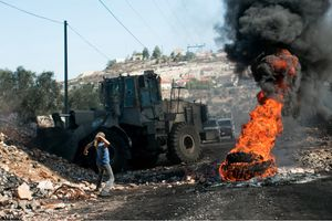 A Palestinian protester throws a stones at an Israeli bulldozer during a protest against the occupation in the West Bank village of Qaddum, 2012.