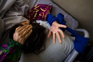A mother places her hand on her daughter's head inside a mental hospital in Kabul. Due to decades of war, it is estimated that roughly half of Afghanistans population suffers from some kind of mental health issue, requiring medical attention. © Michael Christopher Brown