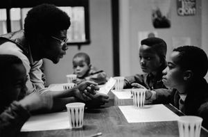 "November, 1970 - Chicago, Illinois, USA: Free Breakfast Program.  Panther Jerry Dunigan, known as ""Odinka"", talks to kids while they eat breakfast on Chicago's south side. The Free Breakfast for School Children Program was a community service program run by the Black Panther Party."