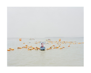 People crossing the Yellow River with a portrait of Mao Zedong, 2011 © Zhang Kechun. Exhibitor: Galerie Paris-Beijing.