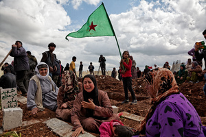 At a cemetery in Kobane, Syria, on 2 April, 2015, Kurdish people sit by the grave as they mourn their loved one, a YPG fighter (Kurdish People's Protection Unit), who was killed during clashes with the Islamic State in one of the frontlines of Kobane, Syria.
