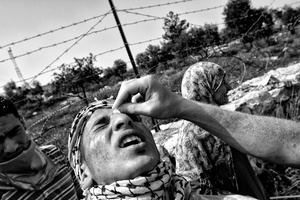 A boy suffers the effects of tear gas during a demonstration in the West Bank. A left-wing Israeli activist swabbed his eyes with an alcohol pad to alleviate the symptoms. Bil'in. April 1, 2011. West Bank, Palestine.
