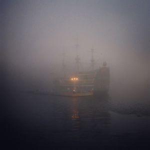 A boat moves in heavy fog in Hakone, Japan.