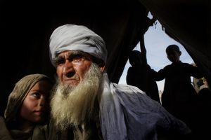 An elderly man holds his granddaughter in their tent at a refugee camp. They were forced to flee their village after U.S. and NATO forces bombed it because, they claimed, it was a Taliban hideout. Surobi, Nangarhar Province, Afghanistan. Feb. 7, 2009. © Paula Bronstein/Getty Images