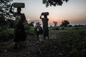 Florence and Lynda fetch water before dinner. They are joined by Mwanje Bernard in the middle