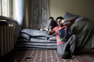 In his room he shares with his nephew, Abdullah (25) talks with his girlfriend. He uses Viber, WhatsApp and Facebook for chating. He has never met her, she lives in South Africa | Kabul, Afghanistan 2013 © Sandra Calligaro