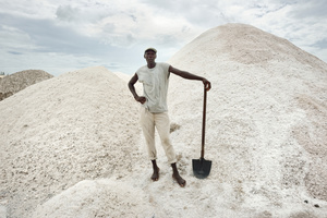 A worker poses in front one of salt mountains that have to be removed and packaged.