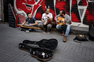 """Fadel (center) studied music production and sound engineering. He is the founder of a radio program called """"Yasmin Shaam"""", where he plays music as well as speeches about justice, equality and freedom.  In Syria, he was arrested three times for opposing the government. To save his life, he migrated to Istanbul where he continues his protest. © Turjoy Chowdhury"""