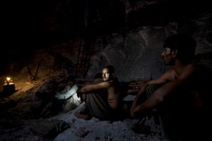 Salt miners take a rest inside the darkness of the Khewra salt mine.