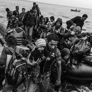 A boat packed with refugees lands on the coast of Lesbos, Greece.