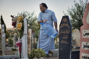Jaser, from Falluja, washes his father's grave in the new part of Shaqlawa's graveyard. His father died two months after arriving to Shaqlawa as a displaced person, early 2014. 28/08/15. Shaqlawa, Iraq.