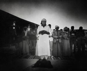 Negev Desert, Israel (2005). Unrecognized desert village. Dusk. Men praying.