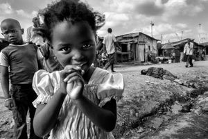 © Tony Corocher - Contrasts: Curiosity & diffidence, desperation & indifference. Through the streets of Mathare Slum (Nairobi). The contrast between the innocent beauty of the young girl, the vivid diffidence of the boy behind her, the finality of the desperation shown by the man on the ground behind her and the indifference of the people passing by… this is the ensemble of feelings that runs thro