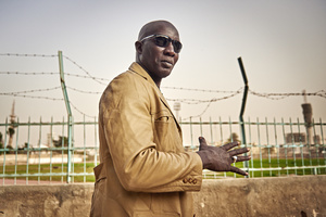 Ex-wrestler Lac de Guiers poses in front of the Mar Diop stadium on March 29, 2015. Here his fight against the wrestler Commando wrote Wrestling history in Senegal. With his targeted, hard punches Lac de Guiers sent the much taller  favourite by knock out to ground. Today he's the owner of a Wrestling school and lives very peacefully with his family, a sheep, a few pigeons and his parrot.