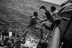 Migrants climb on board of a rescue ship by Doctors without Borders to escapetheir sinking rubber dinghy. Strait of Sicily, Mediterranean Sea, 21 August 2015.