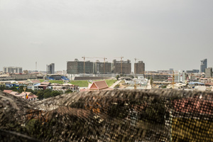 View across Phnom Penh to one of the largest construction sites in the capital, Olympia City. In 2014 a metal bar fell from the 12th storey of the site hitting a 42 year old woman as she rode past on her motorbike killing her instantly.