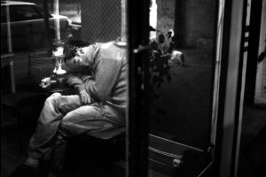 A man sleeping inside a cafe bar in the city center. Athens, Greece  Enri Canaj