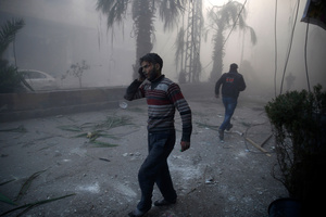 A wounded man walks out of a dust cloud following reported airstrikes in the town of Hamouria, Syria, 09 December 2015.