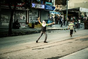 A far left-wing protester of PKK youth organisation YDG-H showing peace sign during clashes with riot police at anti-government demonstration in Istanbul's Gazi neighborhood, Turkey.
