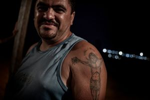 The tattoo on the shoulder of a truck driver working for the building consortium in front of the lights of the main working area of Belo Monte.  © Dario Bosio/Parallelozero