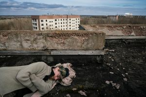Sasha sleeping on the roof of a building in the ghost town of Pripyat. Chernobyl and the infamous Reactor 4 are on his right, just three kilometers away.